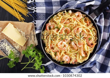 delicious Creamy Parmesan Linguine with Shrimps sprinkled with finely chopped parsley in skillet on black wooden table with piece of cheese and uncooked pasta, horizontal view from above