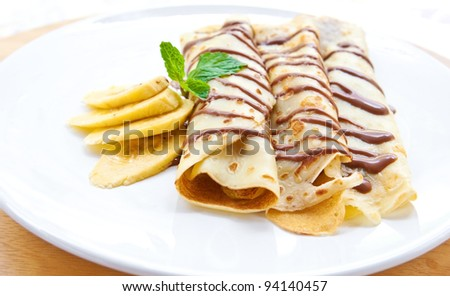Delicious crepe with banana filling with chocolate sauce