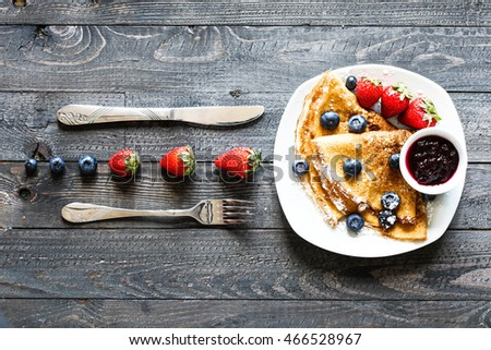 Delicious Crepes Breakfast with Dramatic light over a vintage wood background. An healthy meal of Pancakes with marmalede, blueberries and strawberries. #466528967