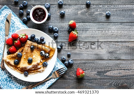 Delicious Crepes Breakfast with Dramatic light over a vintage wood background. An healthy meal of Pancakes with marmalede, blueberries and strawberries. #469321370