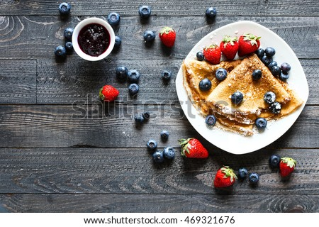Delicious Crepes Breakfast with Dramatic light over a vintage wood background. An healthy meal of Pancakes with marmalede, blueberries and strawberries. #469321676