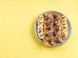 Delicious crepes filled with chocolate hazelnut spread and topped with banana and blueberries. Closeup of the dish on yellow background.