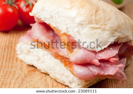 Delicious crispy bacon sandwich on a wooden board