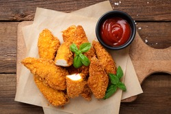 Delicious crispy fried breaded chicken breast strips .