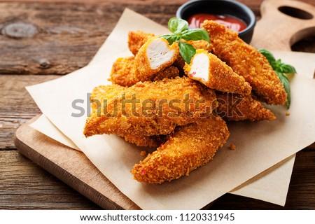 Delicious crispy fried breaded chicken breast strips .