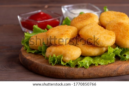Delicious crispy fried chicken nuggets with sauce close-up on the board. Side view. A bunch of nuggets. Сток-фото ©