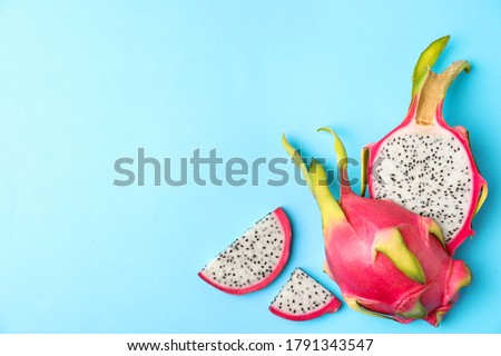 Photo of  Delicious cut dragon fruit (pitahaya) on light blue background, flat lay. Space for text