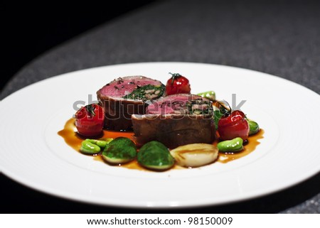 Delicious cuts of roast beef served with vegetables on plate in restaurant