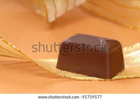Delicious dark chocolate bonbon resting on a gold ribbon
