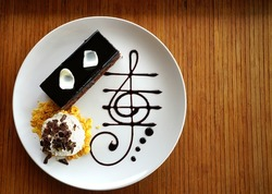 Delicious dark chocolate cake decorated with slice of white chocolate curls, whipping cream and chocolate music note in white plate on wooden table.