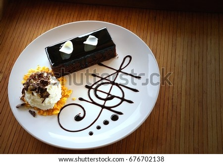 Delicious dark chocolate cake decorated with slice of white chocolate curls, whipping cream and chocolate music note in white plate on wooden table. #676702138