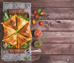 Delicious deep fried south Indian Samosa pies with meat, lettuce, mint chutney and tomato sauce on a wooden background in rustic style, empty place for text, top view