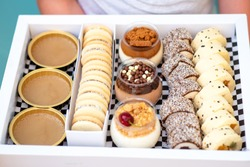 Delicious dessert chocolate and vanilla mousse in a glass jar. Fresh fruit sushi, alfajores, macaroons and creme brulee in white box. Happy hour, delivery. Selective focus.