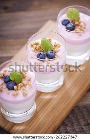 Delicious dessert, flakes flooded in two flavors yogurt with blueberries and fruit on a wooden board. dSLR photo