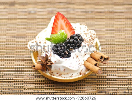 Delicious dessert with whipped creme, strawberry, blackberry and cinnamon