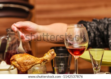 Delicious dinner ideas, meat food concept. Human hand holding cooked chicken leg on fork #1142537876