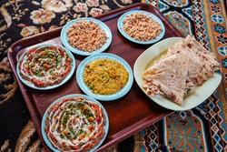 Delicious dishes of traditional omani food served on carpet in traditional restaurant, Oman
