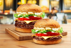 Delicious Double Beef Burger consists of Bun Bread Patty Pickle Onion Mayonaisse Ketchup Cheddar Cheese and lettuce in a yellow background