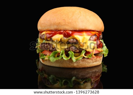 Delicious double cheeseburger with melted cheese and lettuce on a fried crispy bun. Stock photo ©