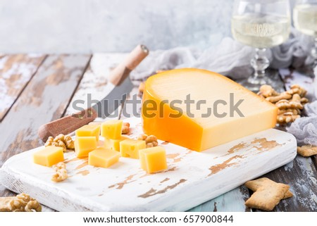 Delicious dutch gouda cheese with cheese blocks, crackers, walnuts and special knife on old wooden table. Copy space.