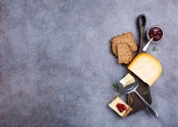 Delicious dutch gouda cheese with cheese slices, multigrain bread, strawberry jam and special knife on old wooden board. Healthy food concept with copy space.