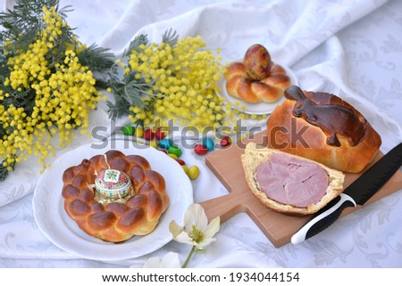 Delicious Easter breads: small braided breads - Easter nests with an egg and Easter ham baked in sweet bread and decorated with dough in a shape of bunny; hellebores and mimosa in background stock photo