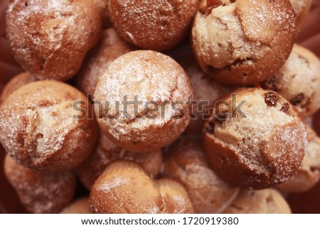 Delicious English muffins with raisins sprinkled with icing sugar. Cupcakes with biscuit air pastry and dried grapes. Hill of ruddy baked homemade sweet buns. Close-up, selective focus.Yummy cookies. Stock photo ©