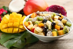 Delicious exotic fruit salad and ingredients on wooden table