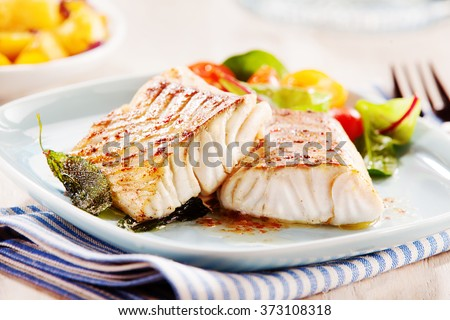 Delicious fillets of pollock or coalfish cooked in a spicy marinade and served with fresh salad and baby potatoes as a seafood appetizer to dinner #373108318
