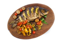Delicious fish baked fish with lemon and condiments. Delicious baked fish on a street background. Grilled vegetables and baked fish on the table. Isolate baked fish