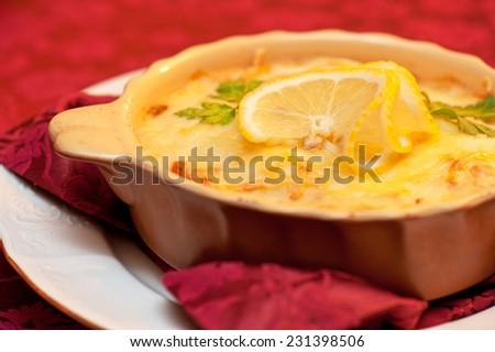 Delicious fish stew dish closeup. At russian dishes - skoblyanka.