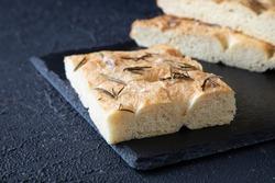 Delicious focaccia - Italian bread - according to a traditional recipe consisting of flour, olive oil, water, yeast, Fleur de Sel, sugar, rosemary