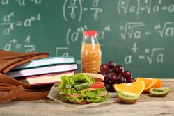 Delicious food, fruits and bottle of juice on wooden table against chalkboard background