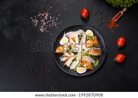 Delicious fresh caesar salad with chicken meat, breadcrumbs, tomatoes and lettuce leaves. Healthy food
