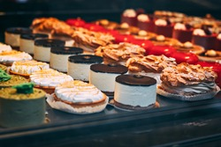 Delicious fresh cakes in the pastry shop behind the glass