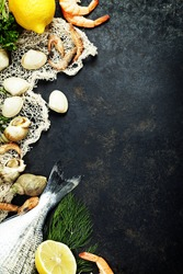 Delicious fresh fish and seafood on dark vintage background. Fish, clams and  shrimps with aromatic herbs, spices and vegetables - healthy food, diet or cooking concept