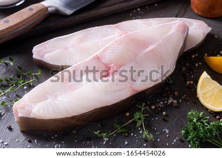 Delicious fresh halibut steaks on slate with lemon and parsley.