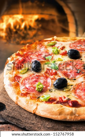Delicious fresh oven baked spicy salami or pepperoni pizza with melted cheese and olives on a wooden board in front of a roaring fire in a pizza oven at a pizzeria