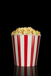 delicious fresh popcorn in classic red and white paper striped bucket isolated over the black background.