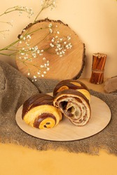 Delicious fresh puff pastry buns with chocolate on wooden background