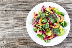 delicious fresh salad of prawns and mixed lettuce leaves - baby spinach, arugula, radicchio rosso in the white dish on the old wooden table, rustic style, top view