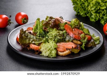 Delicious fresh salad with fish, cheese, tomatoes and lettuce leaves. Healthy food