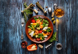 Delicious fresh salad with seafood on the old wooden background, top view