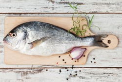 Delicious fresh sea bream fish on wooden kitchen board with onion, rosemary and colorful peppercorns on white textured wooden background. Culinary healthy cooking.