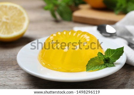 Delicious fresh yellow jelly with mint on wooden table Stock photo ©