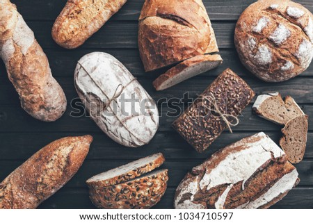 Delicious freshly baked bread on wooden background #1034710597