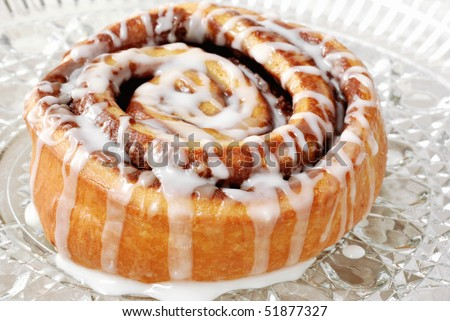 Delicious freshly baked cinnamon roll on crystal plate.  Macro with shallow dof.