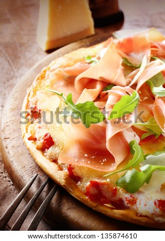 Delicious freshly baked Italian prosciutto ham and rocket pizza with a sprinkling of parmesan cheese served whole on a round wooden board. More pizza at my port.