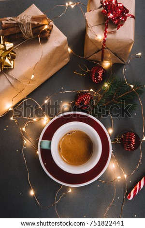 Shutterstock Delicious freshly brewed morning espresso coffee with beautiful crema on the dark grey background with spruce branches, holiday presents, candy cane, red Christmas decoration balls and fireflies, top