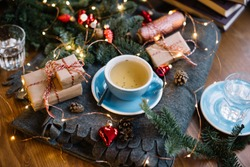 Delicious freshly brewed thyme tea in a blue cup standing on the warm cozy piled cover with red christmas ornamental hearts, little wrapped gifts, fireflies, pine cones on the wooden table background